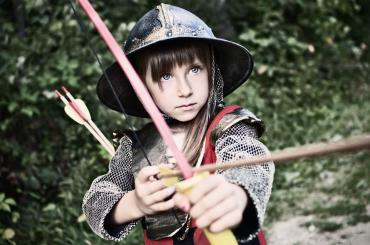 young girl in medieval armour with bow and arrow