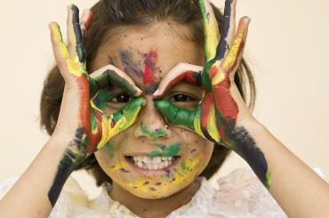 child with paint on her hands and face smiling