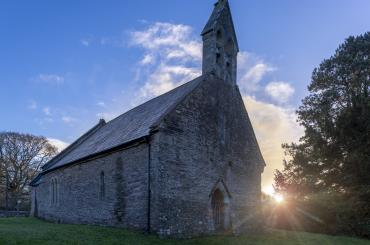 y tu allan i'r eglwys, gyda'r haul yn gosod / outside of the church, with the setting sun